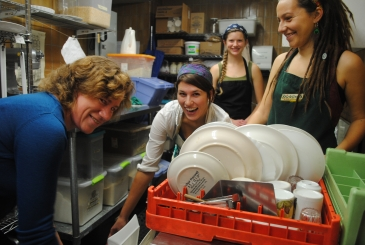 Staff smiling by a dishwasher