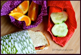 A purple red and green beewswax food wrapper, each with different patterns, sitting open on top of a wooden table, all with a different food sitting in them - orange, cucumber and a sandwich.